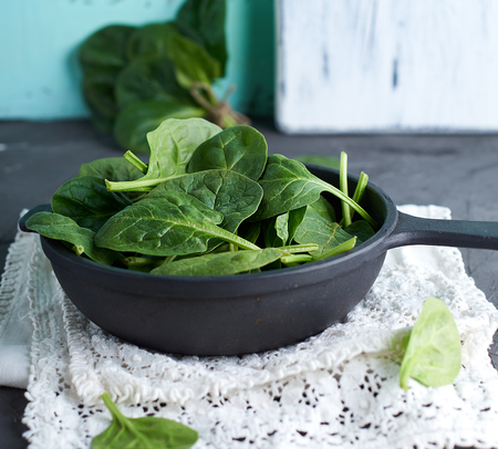 fresh green spinach in a round cast-iron frying pan on a black background, top view