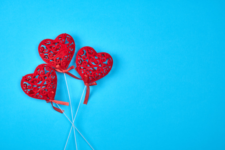 three red carved hearts on a stick on a blue background,  copy space Stock fotó