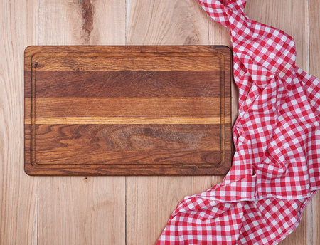 Empty old wooden kitchen cutting board and a red towel on a brown table, the view from the top Фото со стока