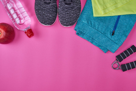 women's sportswear and fitness items on a pink background, copy space, top view