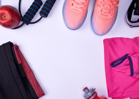sports textile shoes and other items for fitness on a white  background, top view