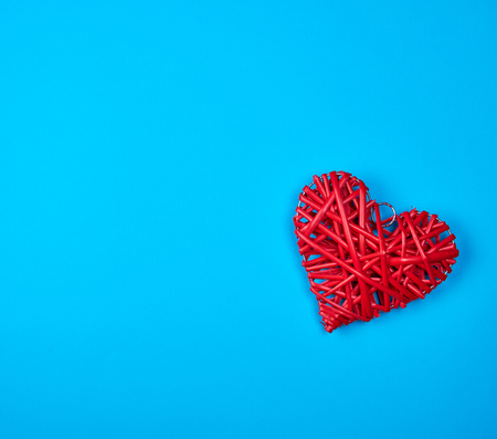 wicker red heart on a blue background, copy space