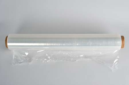 coiled roll of transparent polyethylene for food packaging on a white background