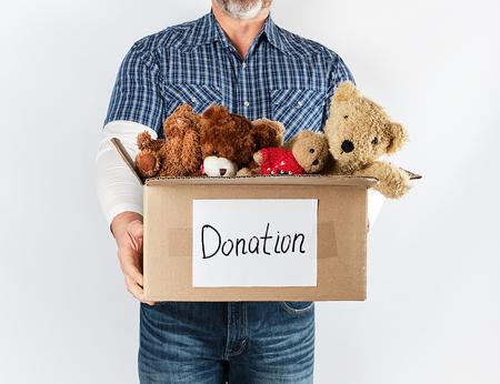 ein Mann in blauem Hemd und Jeans, der eine große braune Pappschachtel mit Kinderspielzeug hält, Hilfskonzept für die Armen, weißer Hintergrund,