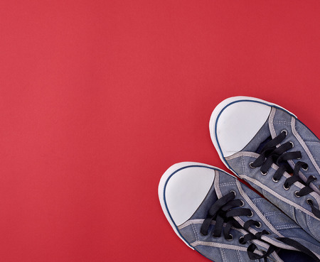 pair of black old textile sneakers  on a red background, copy space