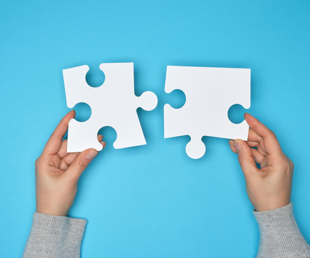 two female hands holding big paper white blank puzzles on a blue background, concept of business Stock Photo