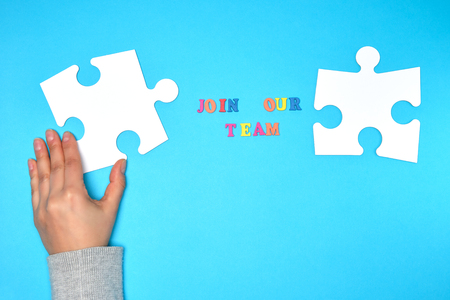 women's hand hold large white puzzle and the inscription join our team on a blue background, the concept of recruitment