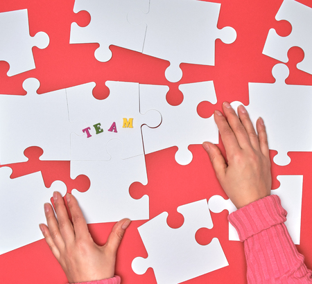 female hand puts white big puzzles on a red background, the inscription team. concept of recruitment in the company