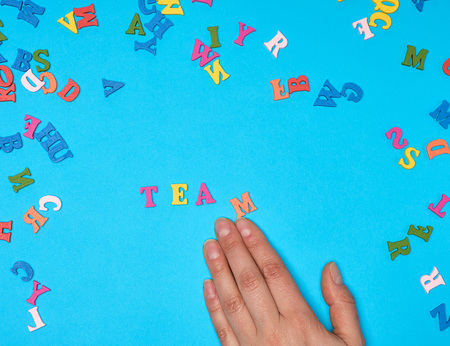 female hand and multicolored wooden letters of the English alphabet on a blue background,  inscription team