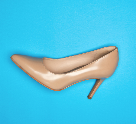 one beige women´s shoe with a thin heel, blue background Imagens - 120137944