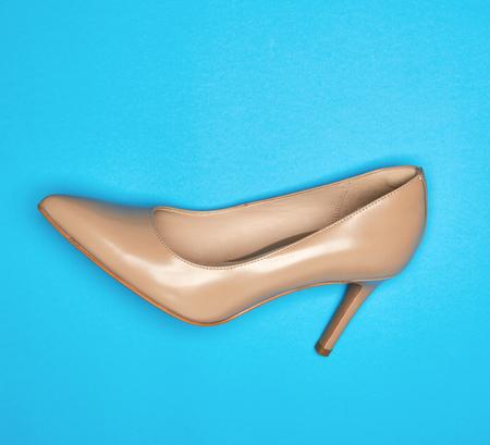 un zapato de mujer beige con tacón fino, fondo azul