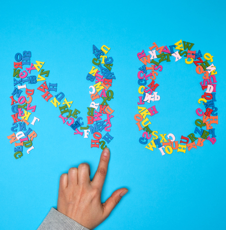 word no from multicolored small wooden letters on a blue background,  female hand holds one figure