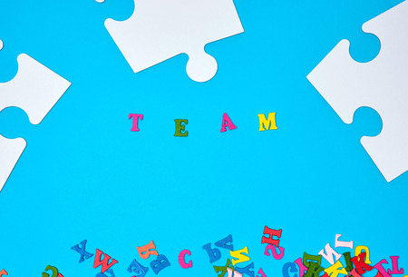 big paper blank white puzzles on a blue background, inscription team, concept of recruitment