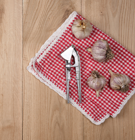 unpeeled fresh garlic fruits and an iron press on a wooden background