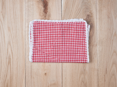 red textile towel in a white cell on a wooden  background, copy space Фото со стока