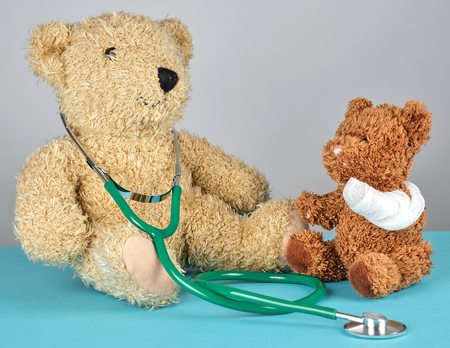 teddy bear with bandaged paw and stethoscope, pediatrics concept