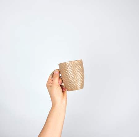 brown ceramic cup in a female hand on a white background,  hand is raised up
