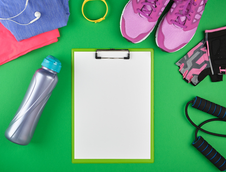 sports women's clothing for sports and fitness, top view, green background, in the middle of the holder for the paper with empty white sheets