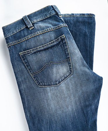 folded blue mens jeans on a white background, top view