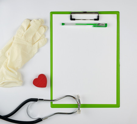 medical stethoscope and green paper clipboard  on a white background, copy space 版權商用圖片