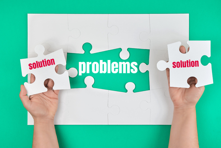 female hand holding white puzzle with the word solution, process of closing the missing element with the word problem, conceptual business background