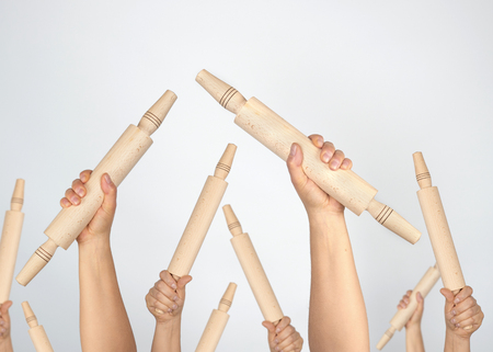 many hands raised up and holding kitchen wooden rolling pins on gray background, concept of riot 写真素材