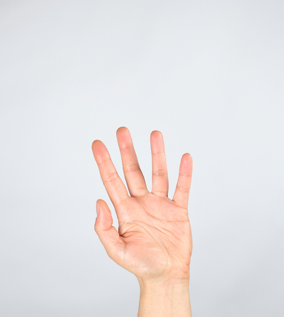 mano femenina levantada sobre un fondo blanco, palma abierta