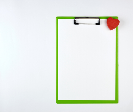 paper clipboard and red heart on a white background, top view