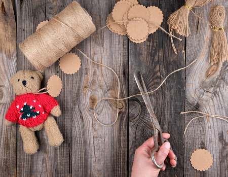 female hands cut brown rope for tags, toy making process, gray wooden table 版權商用圖片