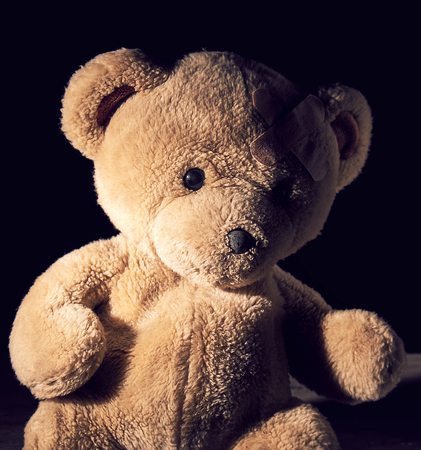 old brown teddy bear is sitting ,  plaster is glued on his forehead, black background