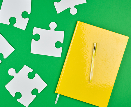 closed yellow notebook and pen, next to it are large empty white paper puzzles, green background, top view