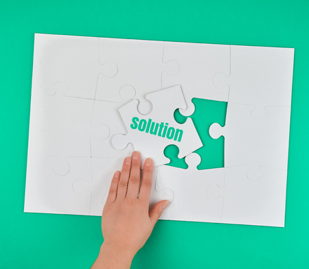 female hand holding white puzzle with the word solution, process of closing the missing element, conceptual business background
