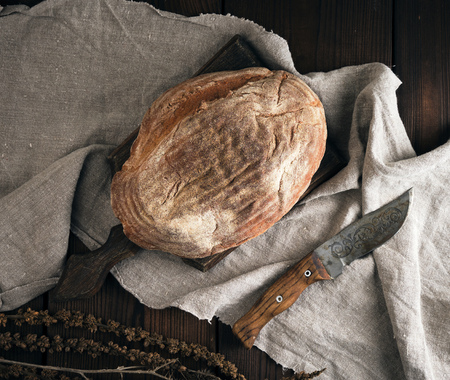 baked oval bread made from rye flour on a wooden cutting board, knife lies next to it, top view