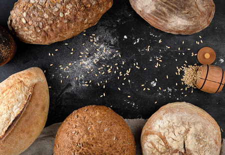 baked different loaves of bread on a black background, top view, copy space