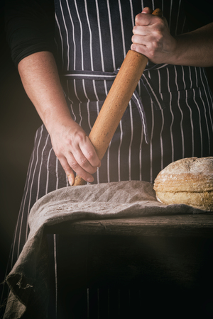 woman in an apron holds a wooden rolling pin next to baked round bread on a wooden table, dark background,  suns rays from the window
