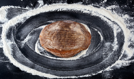 baked bread and white wheat flour scattered on a black table, top view