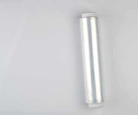 Aufgerollte Rolle aus transparentem Polyethylen für Lebensmittelverpackungen auf weißem Hintergrund, Kopierraum Standard-Bild