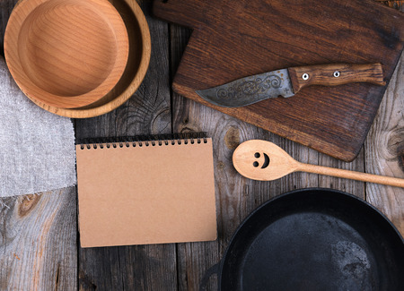 empty black round frying pan, cutting board  and spoon  on a  wooden table, top view Banco de Imagens