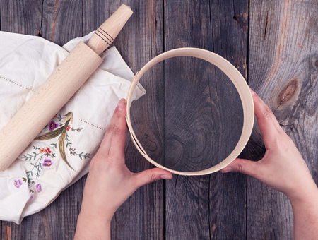 female hands holding a round wooden sieve for flour, next to an wooden rolling pin on a gray table