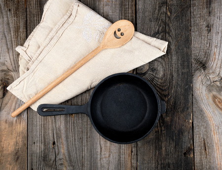 empty black round frying pan with  handle and wooden spoon on a  wooden table, top view