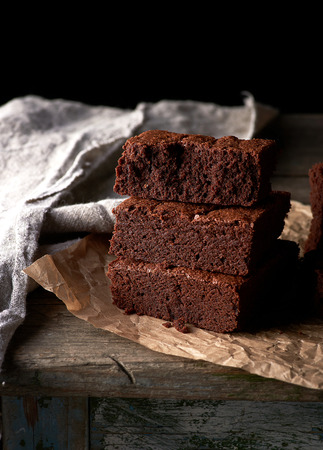 A stack of baked square pieces of chocolate brownie cake on brown parchment paper, black background Stok Fotoğraf - 122593986