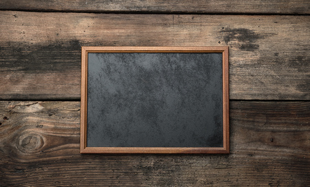 wooden empty chalk board on a brown wooden background, copy space