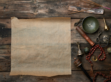 tibetan religious objects for meditation and alternative medicine, empty brown sheet of paper on a brown  wooden background, top view