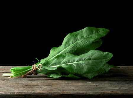 fresh green leaves of sorrel are bound in a bunch on a wooden table, black background