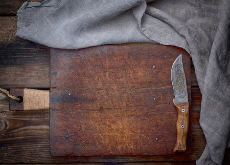 very old empty brown wooden cutting board with handle and kitchen napkin, top view