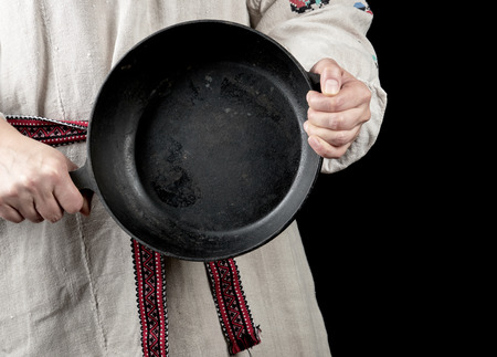woman in a gray linen dress holds a round cast-iron pan, black background Banco de Imagens