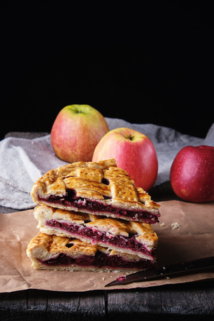 three baked pieces of cake with cherries lie on brown paper, wooden table