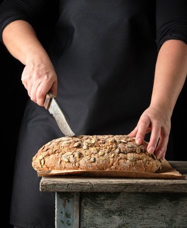 female hands hold oval baked rye bread with pumpkin seeds, dark background Stock Photo