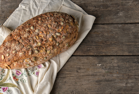 baked oval bread made from rye flour with pumpkin seeds on a gray linen napkin, top view, copy space Banco de Imagens