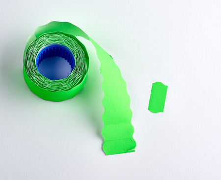 Coil with green empty sticky price tags on white background, top view